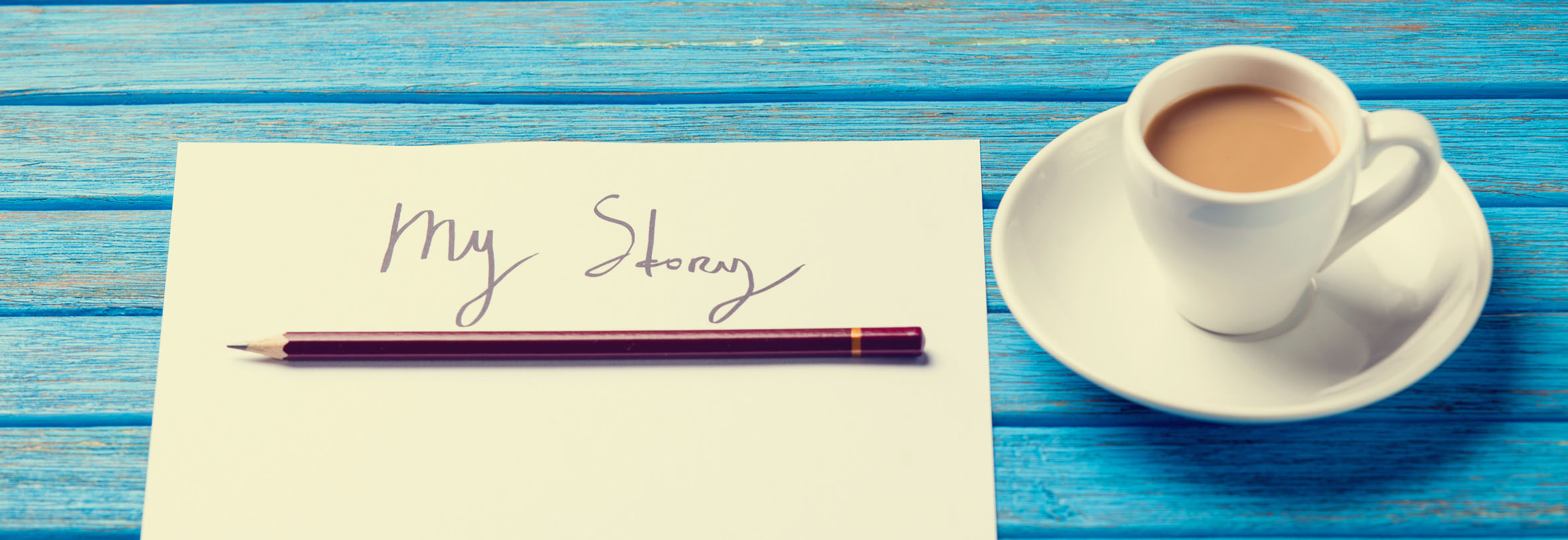 pencil and paper with My Story words near cup of coffee on blue wooden table